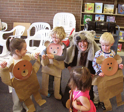 Children wearing bear bodi-puppets